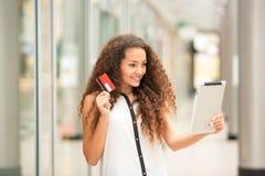 Härlig ung flicka som betalar vid kreditkorten för Fotografering för Bildbyråer