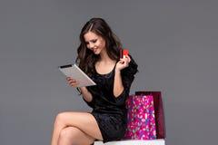 Härlig ung flicka som betalar vid kreditkorten för Arkivfoton