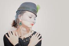 Härlig ung flicka som ha på sig en hatt med en skyla Royaltyfri Bild