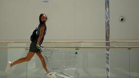 Härlig ung flicka som har rolig ridning på shoppingvagnen på supermarket Ultrarapidskott lager videofilmer