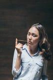 Härlig ung flicka som inomhus tuggar bubbelgum Arkivfoto