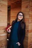 härlig ung flicka som ler hennes pojkvän och innehav gåvan Royaltyfri Bild