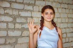Härlig ung flicka som ler med lycka på bakgrund för tegelstenvägg royaltyfri bild