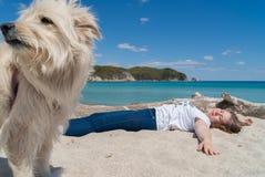 Härlig ung flicka som ligger på sandstranden med hennes hund på solig dag royaltyfria bilder