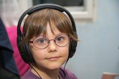 Härlig ung flicka som lyssnar till musik med hörlurar med mikrofon arkivfoton