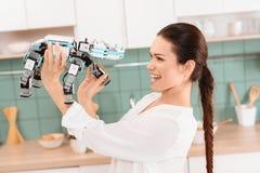 Härlig ung flicka som poserar med en noshörningrobot i ett modernt härligt kök Royaltyfri Bild