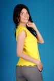 Härlig ung flicka som poserar på en blå bakgrund Arkivbild