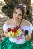 Härlig ung flicka som rymmer en platta med frukter och ett exponeringsglas av vinbäret Royaltyfri Fotografi