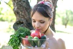 Härlig ung flicka som rymmer en platta med grönsaker och tycker om lukten Arkivbild