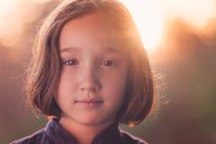 Härlig ung flicka som ser kameran på solnedgången Arkivbild