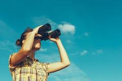 Härlig ung flicka som ser till och med kikare på bakgrund för blå himmel Begrepp för loppferieresa arkivbilder