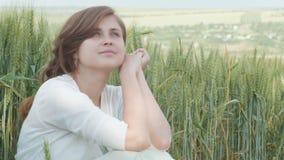 Härlig ung flicka som sitter bland de högväxta gröna spikeletsna av vete i fältet Ung lycklig kvinna som tycker om sommar, harmon lager videofilmer