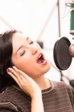 Härlig ung flicka som sjunger i musikstudio Fotografering för Bildbyråer