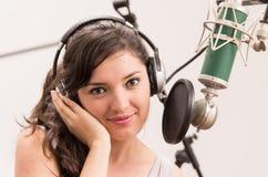 Härlig ung flicka som sjunger i musikstudio Arkivfoton