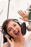 Härlig ung flicka som sjunger i musikstudio Royaltyfri Foto