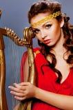 Härlig ung flicka som spelar harpan Royaltyfria Bilder