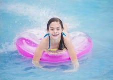 Härlig ung flicka som spelar i pölen i sommartid royaltyfri foto