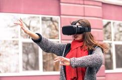 Härlig ung flicka som spelar med virtuell verklighethörlurar med mikrofon eller 3d Fotografering för Bildbyråer