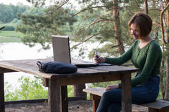 Härlig ung flicka som utomhus använder hennes grafiska minnestavla Royaltyfria Bilder