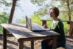 Härlig ung flicka som utomhus använder hennes grafiska minnestavla Royaltyfri Foto
