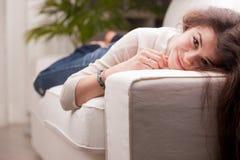 Härlig ung flicka som väntar och ler på en soffa Arkivbild