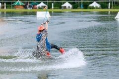 Härlig ung flicka som wakeboarding på sjön Royaltyfria Bilder