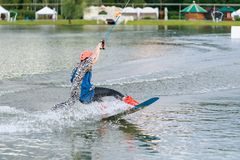 Härlig ung flicka som wakeboarding på sjön Arkivfoto