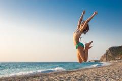 Härlig ung flickabanhoppning på stranden arkivbild