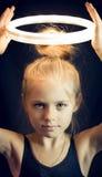 Härlig ung flickagymnast som i höjden rymmer en glödande cirkel Arkivbilder