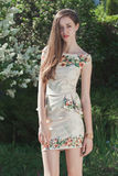 Härlig ung flickamodell som poserar nära blommande lilor på våren Arkivbilder