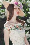 Härlig ung flickamodell som poserar nära blommande lilor på våren Royaltyfri Bild
