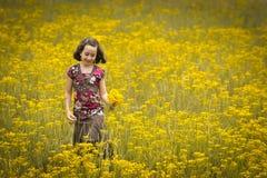 Härlig ung flickaplockning blommar i ett fält Royaltyfri Bild