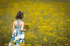 Härlig ung flickaplockning blommar på en solig dag Royaltyfria Bilder