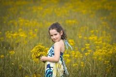 Härlig ung flickaplockning blommar på en solig dag Fotografering för Bildbyråer