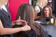 Härlig ung frisör som ger en ny frisyr till den kvinnliga custoen Royaltyfri Foto