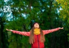 Härlig ung gladlynt kvinnlig modell med armar upp i höst Royaltyfri Bild