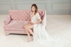 Härlig ung gravid kvinna i vit klänningpeignoir som sitter på den rosa soffan och att visa hennes nakna buk som ser kameran royaltyfri bild