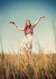 Härlig ung hippieflickadans i fältet på solnedgångtid Royaltyfri Fotografi
