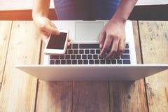 härlig ung hipsterkvinna` s räcker upptaget arbete på hennes bärbar dator, kvinnlign som använder sammanträde för celltelefon på  Royaltyfri Fotografi