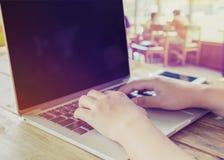 härlig ung hipsterkvinna` s räcker upptaget arbete på hennes bärbar datorsammanträde på trätabellen i en coffee shop Arkivbild