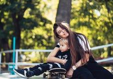 Härlig ung hipstermamma och liten son på skateparken royaltyfri fotografi