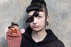 Härlig ung individ, excentrisk kvinna, med att intressera frisyren och piercingar och sneglande pålagda exponeringsglas questioni arkivfoton