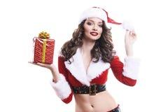 Härlig ung jultomtenflicka med gåvan på vit bakgrund arkivfoton