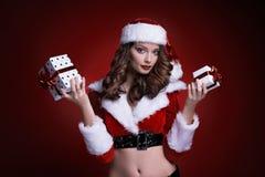 Härlig ung jultomtenflicka med gåvor på röd bakgrund Fotografering för Bildbyråer
