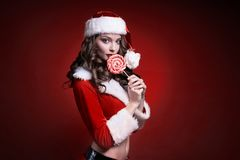 Härlig ung jultomtenflicka med godisen på röd bakgrund Fotografering för Bildbyråer