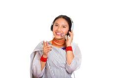 Härlig ung kvinna för Headshot som bär den traditionella andean sjalen, den röda halsbandet och hörlurar med mikrofon, påverkande Royaltyfri Foto
