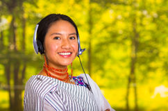 Härlig ung kvinna för Headshot som bär den traditionella andean sjalen och röda halsbandet som poserar för kamera med hörlurar Arkivbild