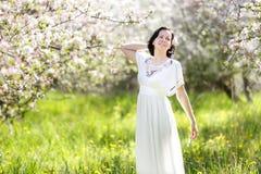 Härlig ung kvinna i äppleblomningträdgård Arkivbild
