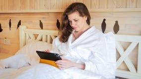 Härlig ung kvinna i badrocken som ligger i säng och arbete på minnestavladatoren Arkivfoton