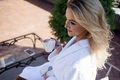 Härlig ung kvinna i badrocksammanträde på terrass- och drinkkaffe Arkivbilder